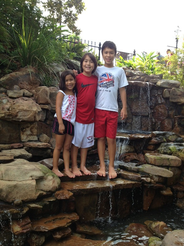 Taking off their shoes and wading in a wishing well waterfall!