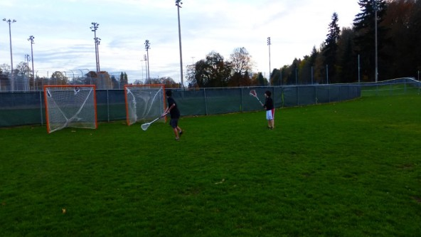 Boys Shooting Lacrosse Together